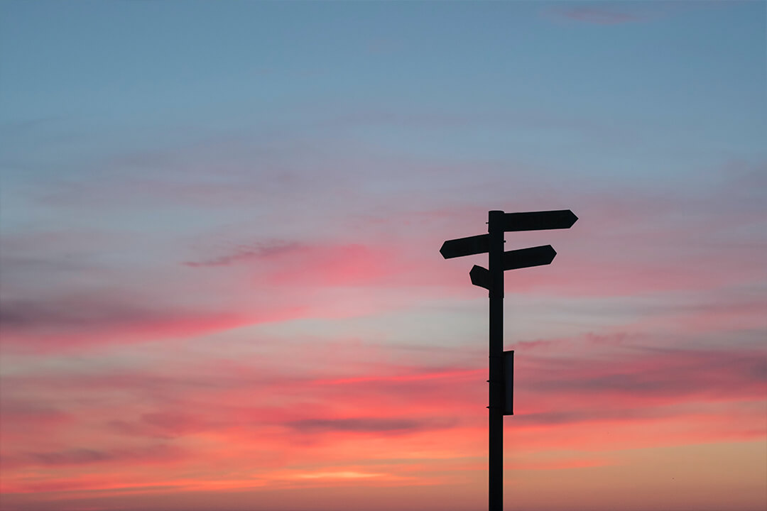Direction signs against sunset sky